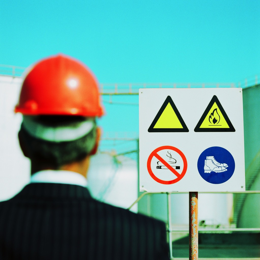 Businessman Wearing a Hard-Hat Looking at a Hazard Sign --- Image by © Royalty-Free/Corbis
